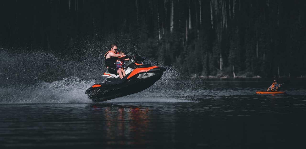man riding a jet ski across river