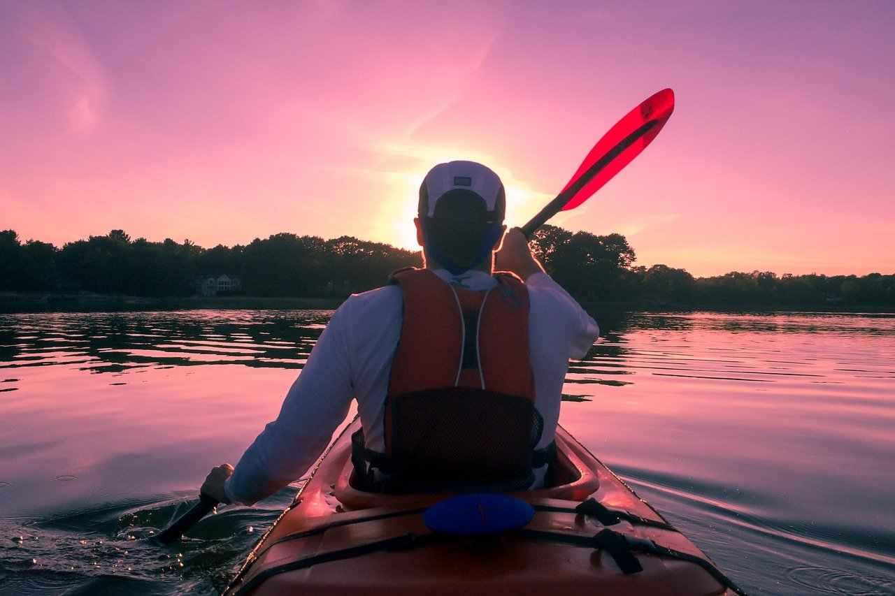 man sitting in kayak during sunset