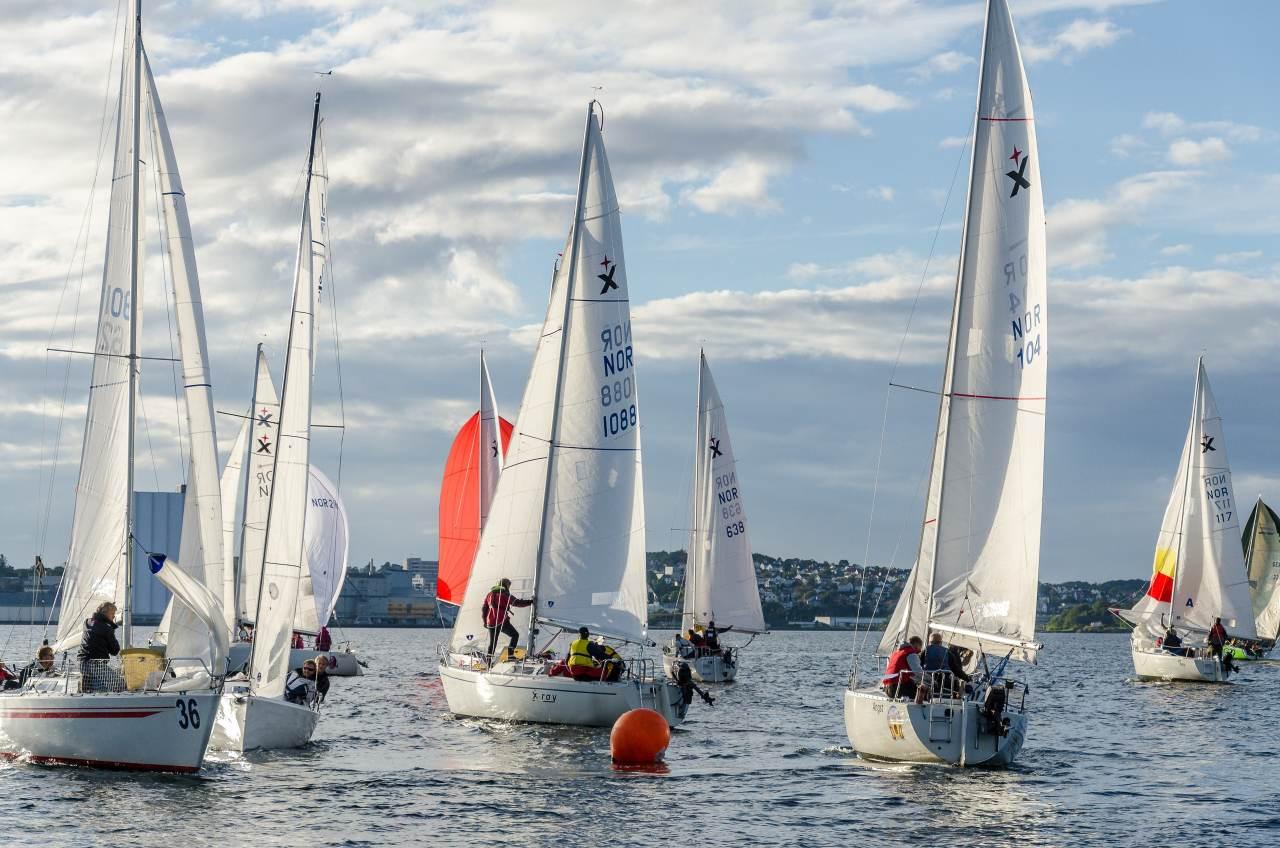 a group of sailing yachts racing